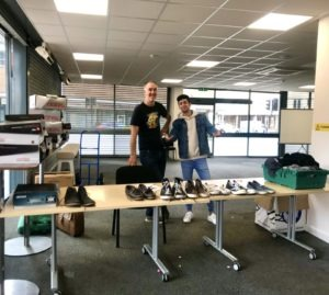 Two volunteers, one of them an asylum seeker, show off their almost-empty 'shoe shop' at our weekly distribution session.