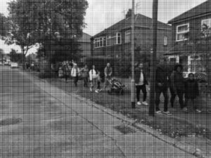 Grainy black and white image, a long line of walkers in a suburban street